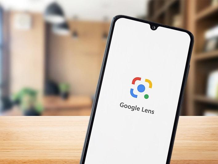 schwarzes Smartphone mit Google Lens Logo am Bildschirm vor Holzfläche und verschwommenem Interieur