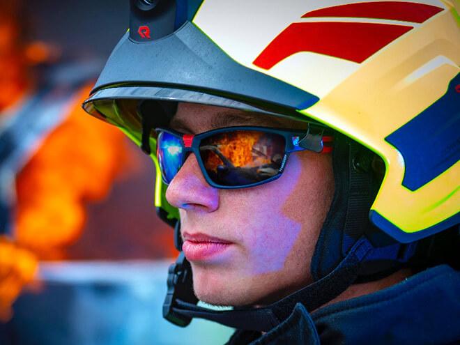 Feuerwehrmann mit einem Helm und einer Sonnenbrille von Hartlauer, verschwommenes Feuer im Hintergrund