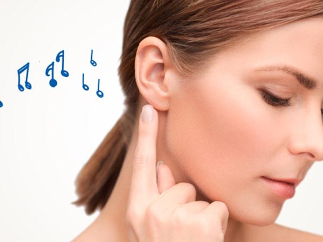 eine Frau zeigt mit dem Finger auf ihr Ohr und daneben blaue Notenschlüssel