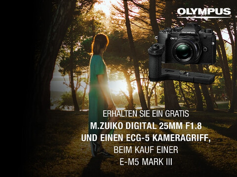 OLYMPUS OM-D E-M5 Mark III mit ECG-5 Kameragriff vor Sonnenuntergang am See mit Wald und Frau mit Aktions-Info
