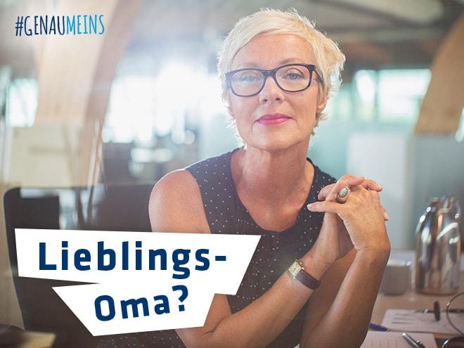 eine junggebliebene Oma mit schwarzer Brille an einem Tisch sitzend