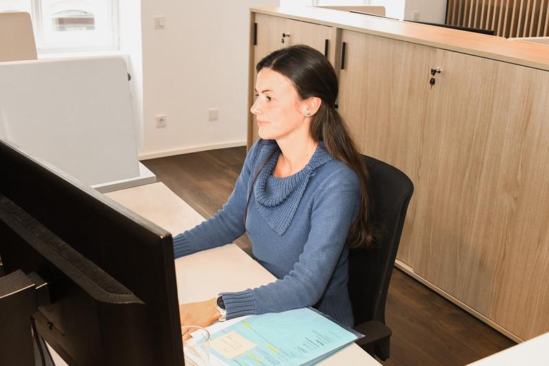 Mitarbeiterin am Schreibtisch vor PC