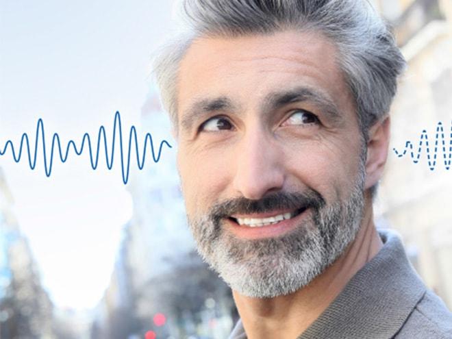 blau visualisierte Schallwellen gehen durch die Ohren eines älteren Herren