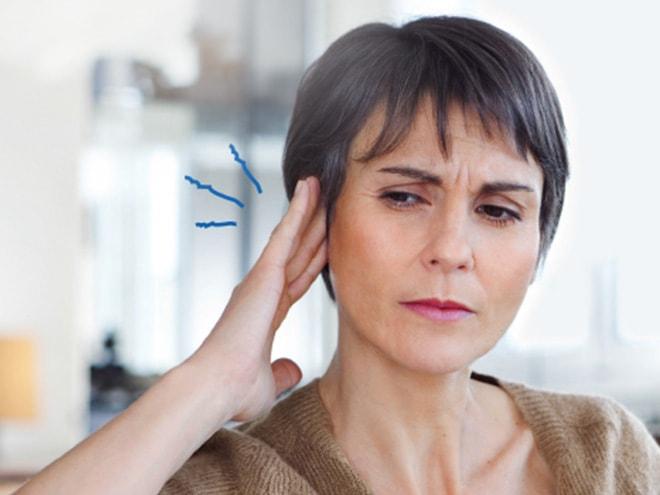 eine ältere Frau hält die Hand ans Ohr mit blau visualisiertem Tinnitus