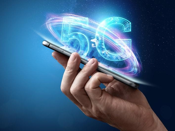 eine Hand mit einem Smartphone, aus dem ein 5G-Hologramm erscheint