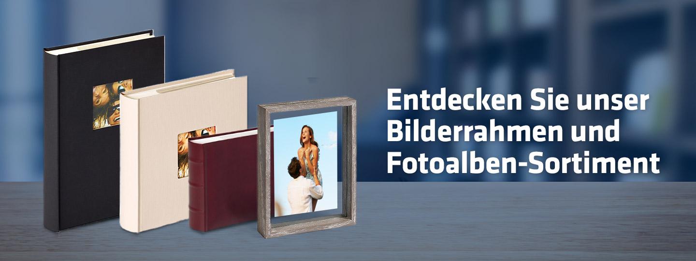 ein Bilderrahmen und drei Fotoalben auf einem braunen Regal, im Hintergrund ein verschwommenes Büro