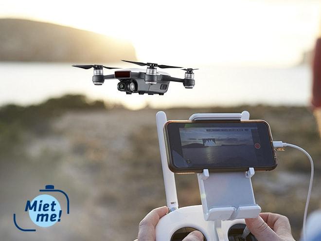 eine Drohne filmt eine Küste und spielt die Aufnahme am Smartphone-Display aus