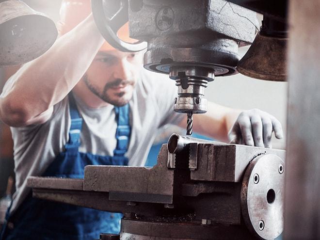 ein Handwerker spannt ein Metallstück in eine Tischbohrmaschine