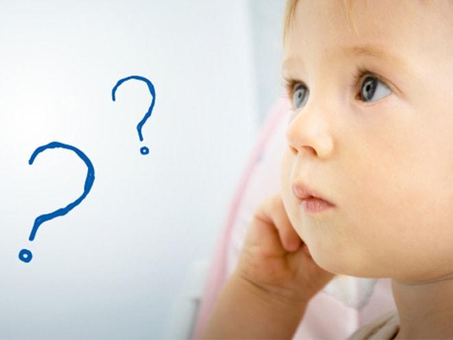 ein nach oben blickendes Baby und zwei blaue Fragezeichen