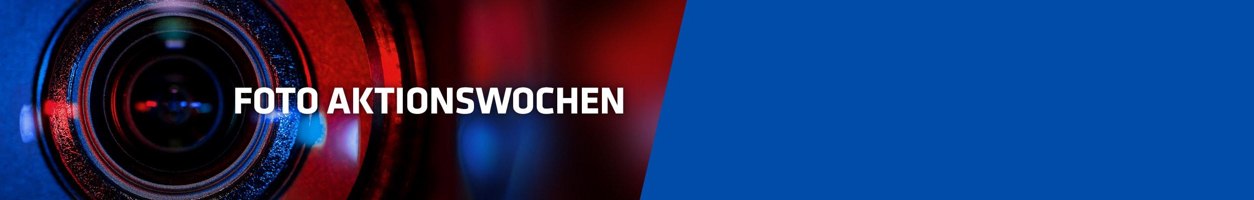 """""""Nahaufnahme von Kameraobjektiv in rot-blauem Licht mit Text """"Fotoaktionswochen"""""""""""