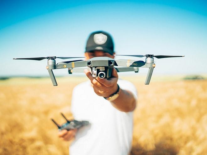 die DJI Mavic Pro Drohne in der Hand eines Mannes vor einem verschwommenen Getreidefeld im Hintergrund