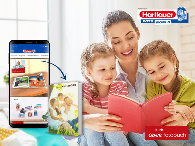 eine Mutter und zwei Kinder blättern in einem Buch, am Smartphone ist die Hartlauer Foto World abgebildet