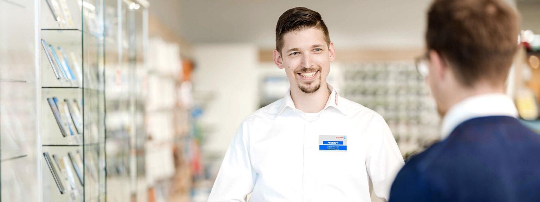 ein lächelnder Hartlauer Mitarbeiter berät einen Kunden