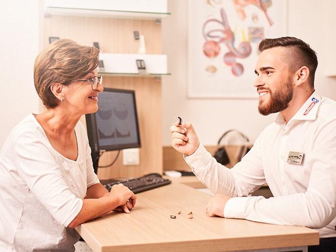 ein Hartlauer Hörakustiker hält ein Hörgerät in den Händen und erklärt einer Kundin Ursachen der Hörminderung