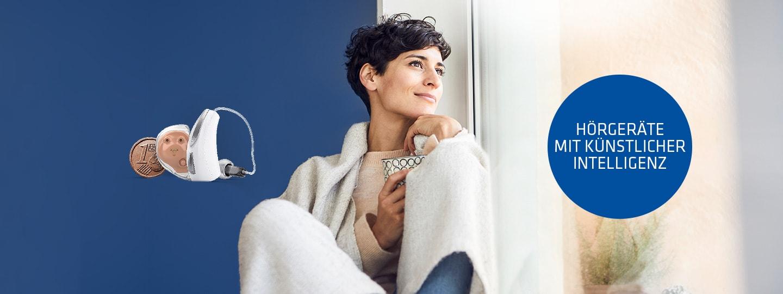 eine Frau blickt verträumt aus dem Fenster mit einer Tasse in der Hand, daneben ein AI Hörgerät von Hartlauer