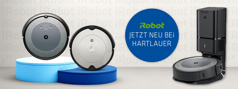 zwei iRobot Roomba Saugroboter auf Podest und ein Modell in Dockingstation