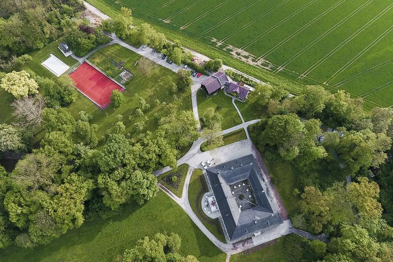 Die Hartlauer Akademie von oben – Gebäudekomplex im Grünen mit Tennisplatz