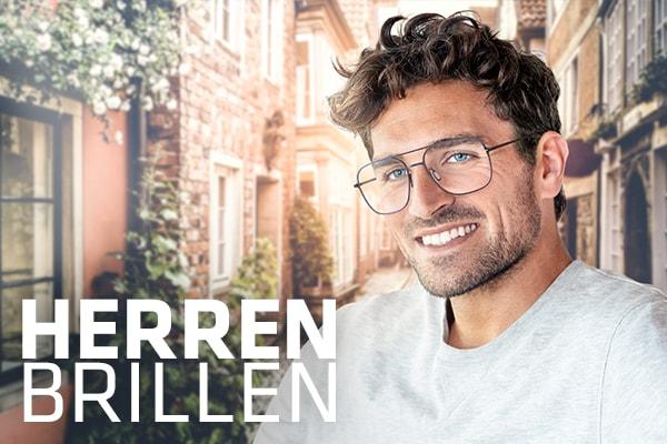 lächelnder Mann mit Hartlauer Brille vor verschwommenem Hintergrund