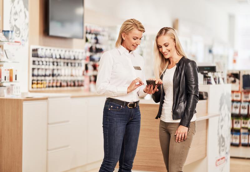 Mitarbeiterin erklaert ein Smartphone