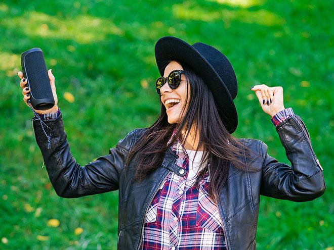 eine auf einer Wiese tanzende Frau hält einen Bluetooth Wlan-Lautsprecher in der Hand