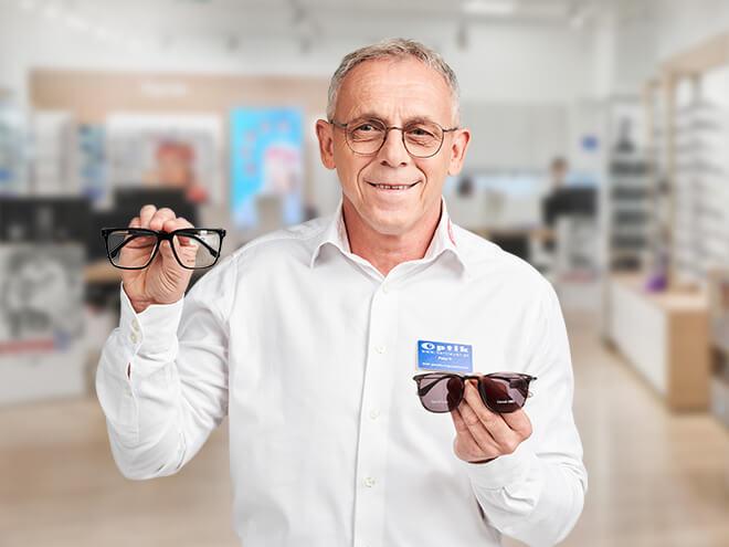ein älterer Hartlauer Optiker hält eine Seh- und eine Sonnenbrille in den Händen