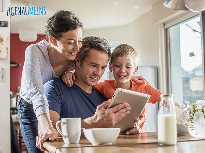 Vater, Mutter und Sohn surfen lächelnd im Internet auf einem Tablet am Küchentisch