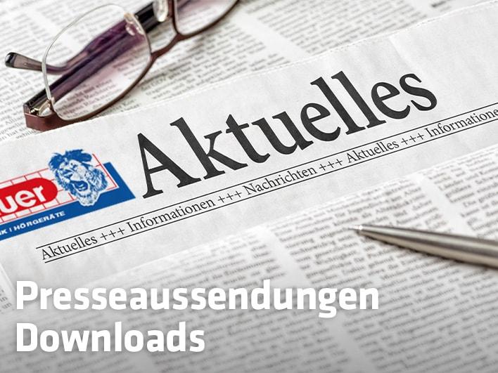 Close-up auf Zeitung mit Hartlauer Logo, Brille und Kugelschreiber