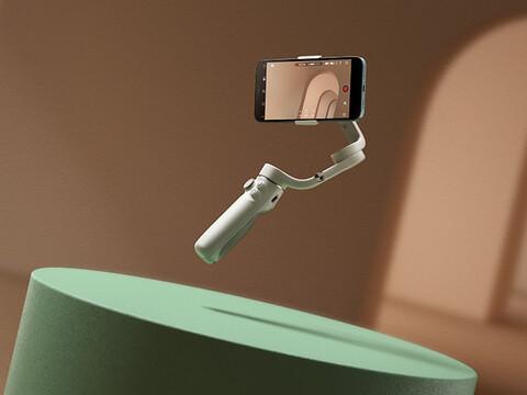DJI OM 5 mit Smartphone vor grüner Bühne