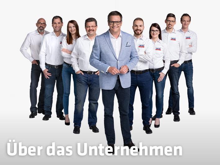 Robert F. Hartlauer mit acht Mitarbeitern und Mitarbeiterinnen hinter ihm in V-Form aufgestellt