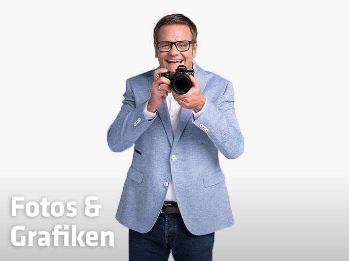 Robert F. Hartlauer in Jeans und hellblauem Jackett zückt Fotoapparat