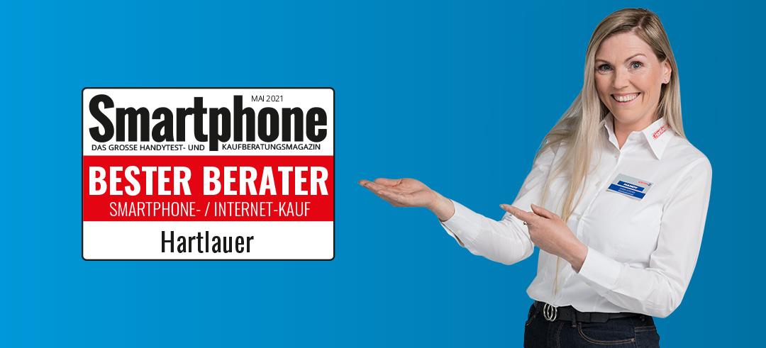 eine lächelnde Hartlauer Mitarbeiterin und das Testsieger-Siegel zu Bester Smartphone-Berater