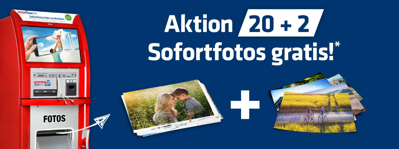 Hartlauer Sofortfoto SB-Druckstation mit Infos zu Sofortfoto-Aktion mit zwei Stapeln von Fotos