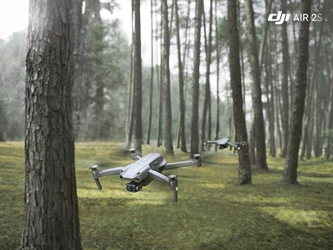 zwei Drohnen des Modells DJI Air 2S fliegen in Bodennähe durch einen Wald