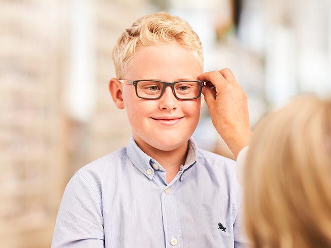 Junge bei der Anprobe seiner Kinderbrille mithilfe von Hartlauer Optikerin