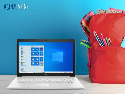 ein HP Notebook von Hartlauer und ein roter Rucksack mit Schulutensilien für den Schulstart