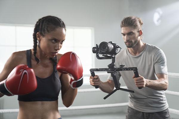ein Kameramann hält eine DJI Gimbal in der Hand und filmt eine Boxerin