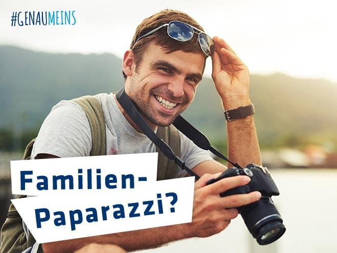 ein lächelnder Mann mit einer Fotokamera von Hartlauer um den Hals in der Natur