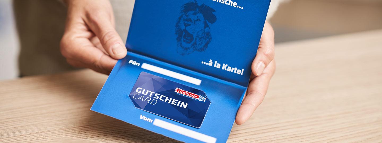 Frauenhände halten Hartlauer Gutscheincard in Geschenkumschlag über hölzerne Tischplatte