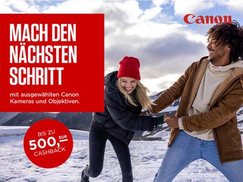 fröhliches Paar hält sich an den Händen in Winterlandschaft mit Info zu 500 Euro Canon Cashback