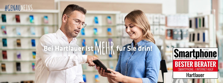 Hartlauer Mitarbeiter berät eine Kundin zu ihrem Smartphone in einem Hartlauer Geschäft