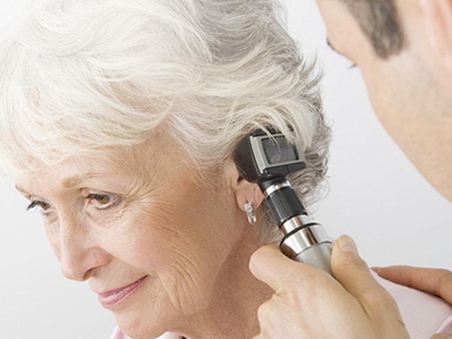 ein Hartlauer Hörakustiker blickt mit einem Gerät in das Ohr einer lächelnden Kundin