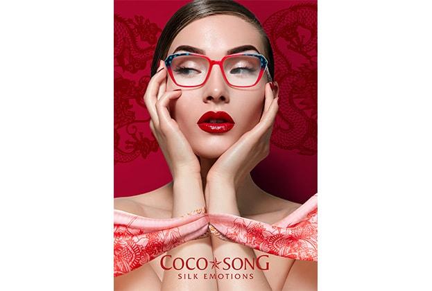 Frau mit ausgefallener Coco Song Brille von Hartlauer vor rotem Hintergrund