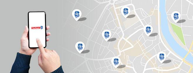 Hand tippt auf Smartphone mit Hartlauer-Logo am Screen neben Stadtplan mit eingezeichneten Hartlauer Geschäften
