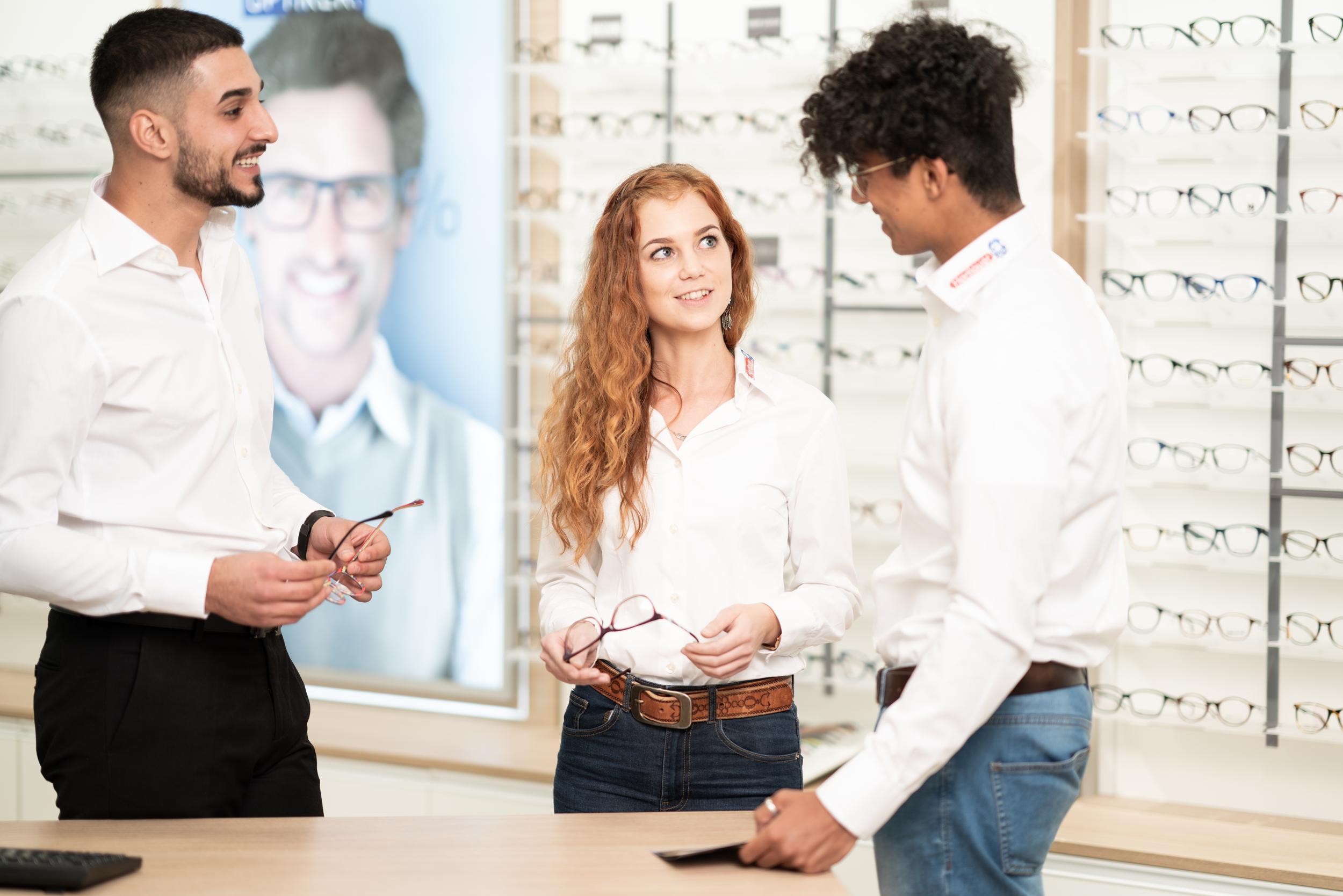 Mitarbeiter unterhalten sich über verschiedene Brillenmodelle