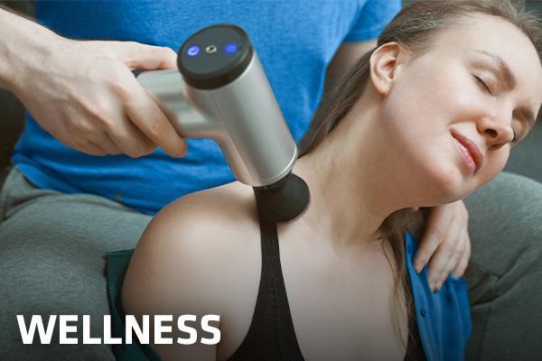 eine Frau wird zuhause  mit einer Massage-Gun von Hartlauer am Nacken massiert
