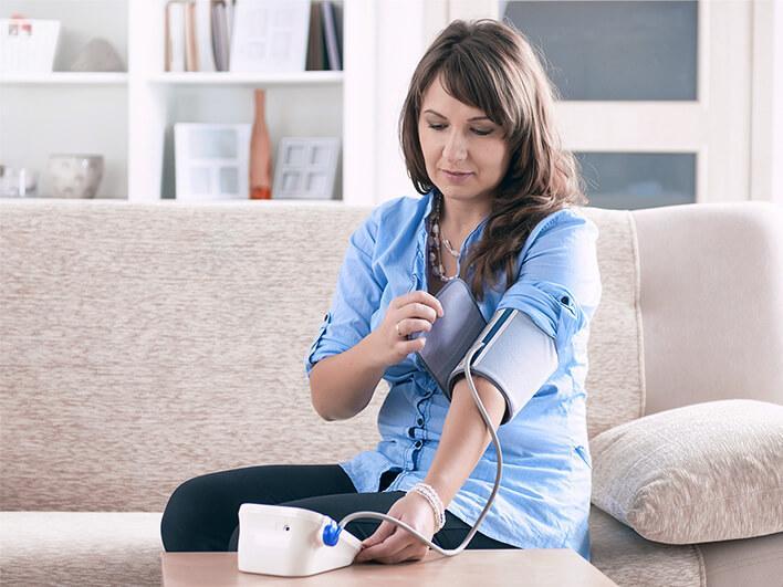 eine Frau misst ihren Blutdruck mit einem Blutdruck-Messgerät von Hartlauer